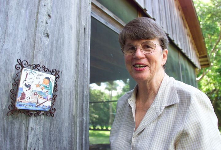 Janet Reno smiles as she greets the media next to a caricature of a journalist and fisherman at the back entrance to her home