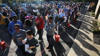 Voters wait in the sunshine to take part in early voting on Sunday, Nov. 6, 2016 at the Summit County Board of Elections in Akron, Ohio. Board workers estimated the total time to vote at 45 minutes. (Mike Cardew/Akron Beacon Journal/TNS via Getty Images)