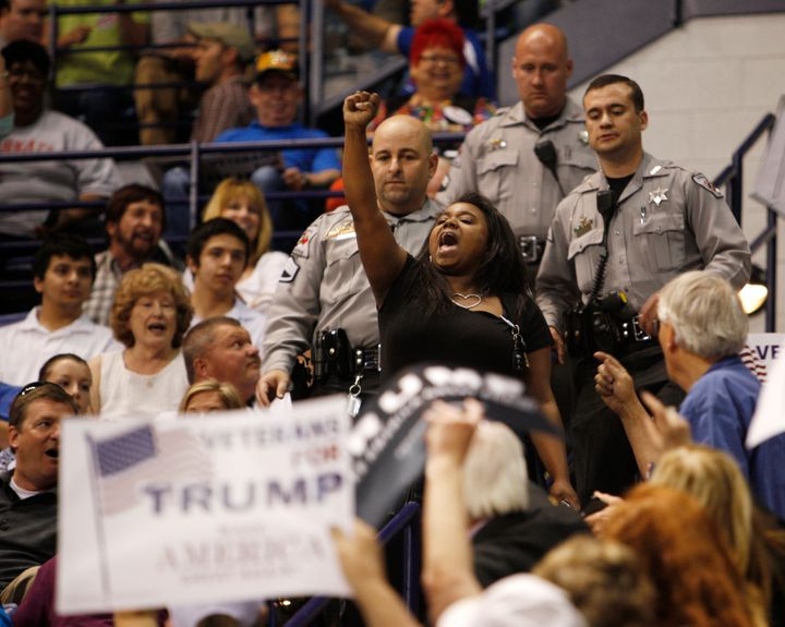 A black demonstrator raises her fist in protest against U.S. Republican presidential candidate Donald Trump as police officer