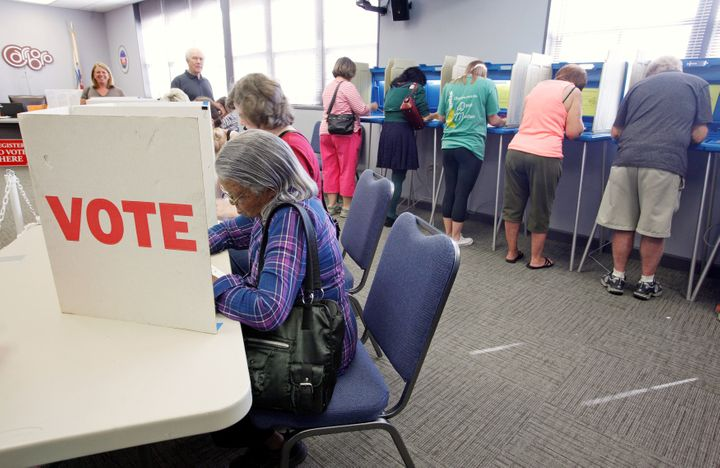 Voters fill in their ballots at a crowded polling station on North Carolina's first day of early voting for the general elect
