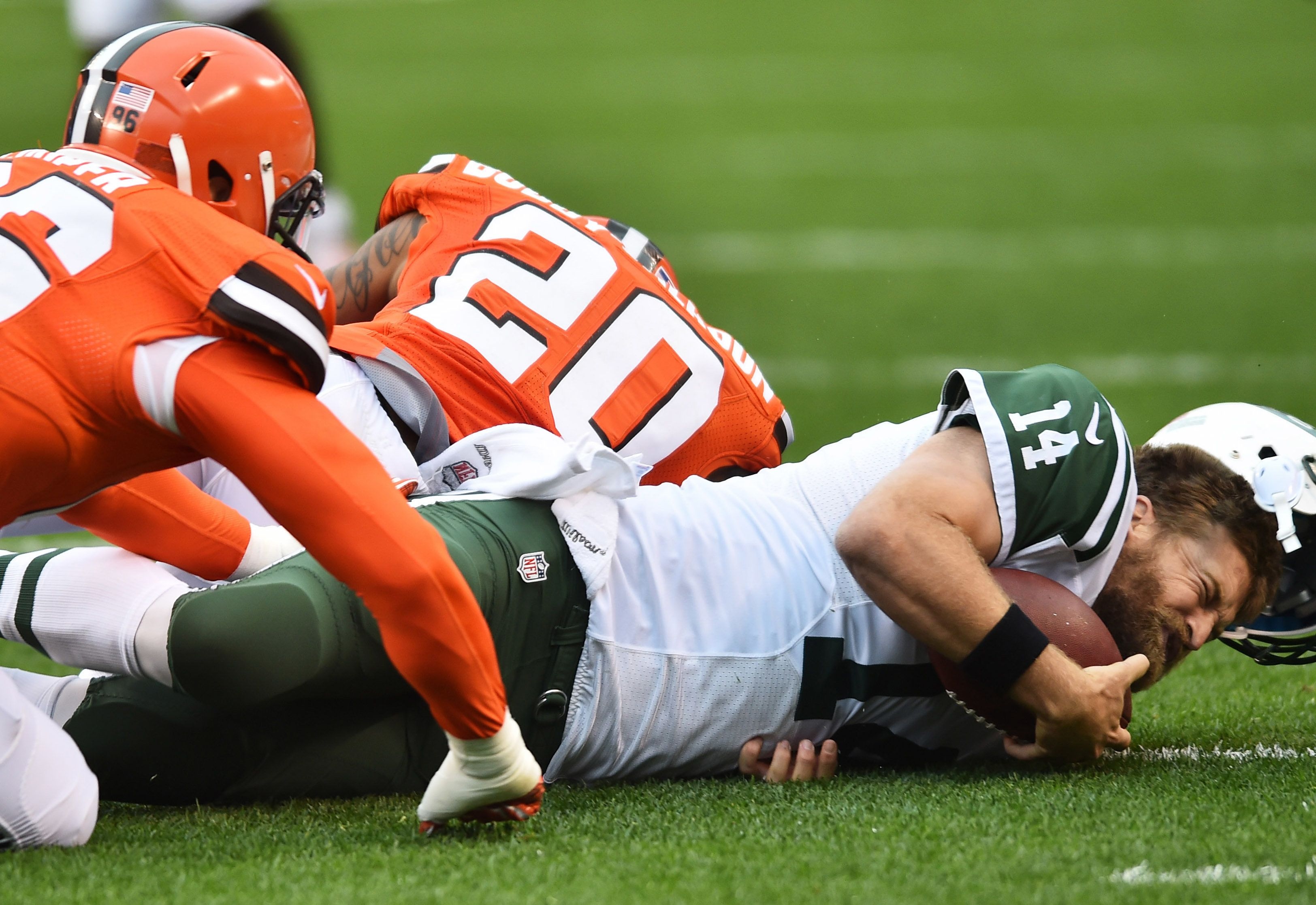 Oct 30, 2016; Cleveland, OH, USA; New York Jets quarterback Ryan Fitzpatrick (14) loses his helmet on a hit by Cleveland Browns cornerback Briean Boddy-Calhoun (20) during the first quarter at FirstEnergy Stadium. Mandatory Credit: Ken Blaze-USA TODAY Sports