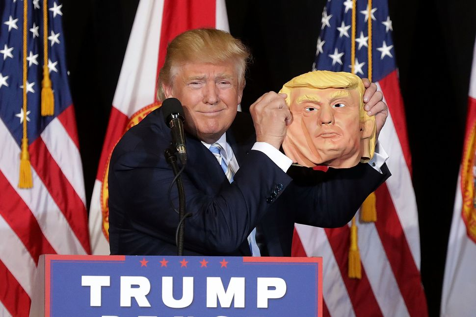 Republican presidential nominee Donald Trump holds up a rubber mask of himself during a campaign rally in the Robarts Arena a