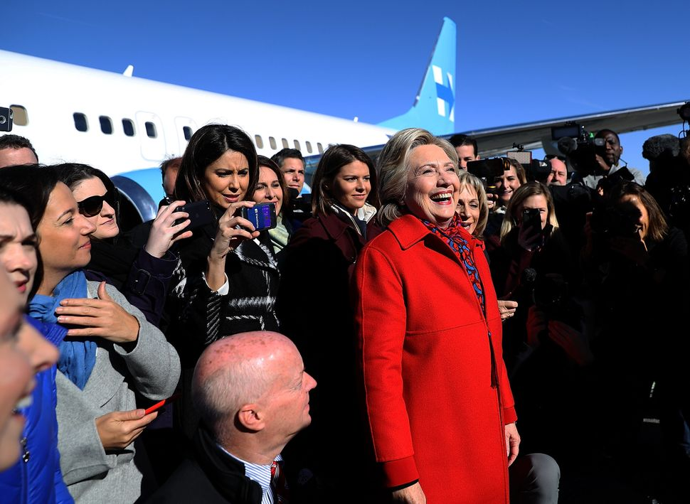 Clinton prepares to take a picture with members of her traveling press corps before boarding her campaign plane at Westcheste