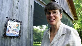 """Former U.S. Attorney General Janet Reno smiles as she greets the media next to a caricature of a journalist and fisherman with the the saying in spanish """"A reporter lives here,"""" at the entrance to the back porch of her Miami home, September 4, 2001. Reno, a life-long resident of south Florida and the daughter of journalists, announced that she will be running on the Democratic ticket for Florida governor in 2002."""