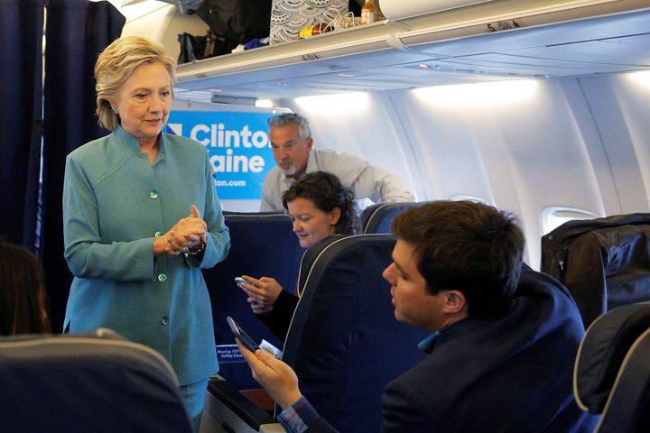 U.S. Democratic presidential nominee Hillary Clinton talks to traveling press secretary Nick Merrill onboard her campaign pla