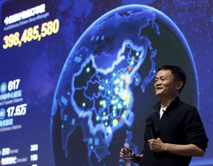 Alibaba founder and chairman Jack Ma gestures in front of a screen showing real-time data of transactions at Alibaba Group's