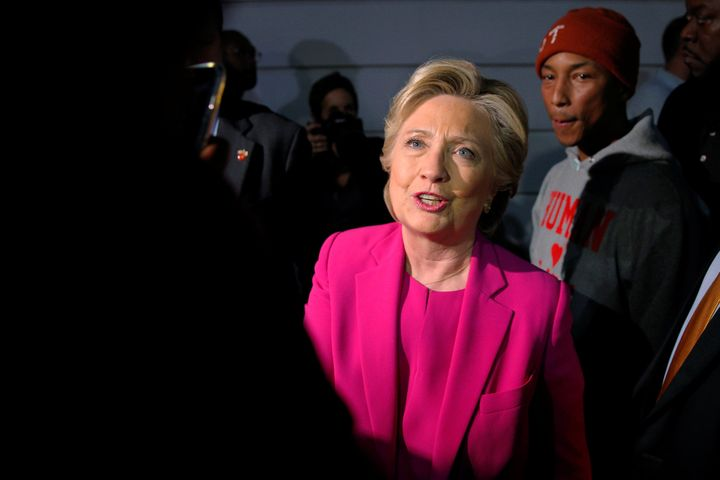U.S. Democratic presidential nominee Hillary Clinton and the musician Pharrell Williams, right, greet students at North Carol