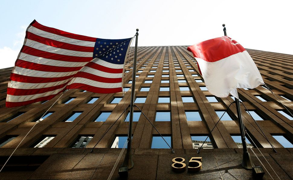 The flags of the U.S. and Singapore hang outside a building in New York.