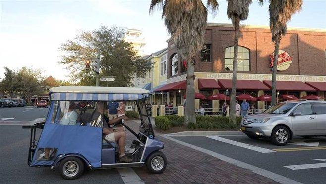Residents ride their golf cart on a street at the Lake Sumter Landing Market Square in The Villages, Florida. Growing numbers