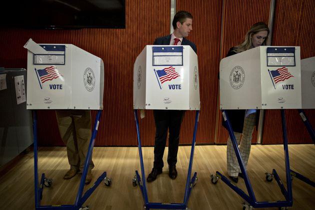 Eric Trump looks towardshis wife Lara Yunaska's ballot paper as she