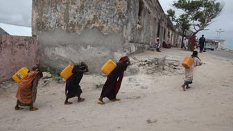 Internally displaced women carry jerry-cans of water on their backs from a well in Somalia's capital Mogadishu September 6, 2011. Famine has spread to six out of eight regions in southern Somalia, with 750,000 people facing imminent starvation, the United Nations said on Monday, and hundreds of people are dying each day despite a ramping up of aid relief. REUTERS/Ismail Taxta (SOMALIA - Tags: DISASTER ENVIRONMENT)