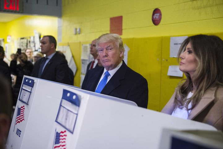 Republican presidential nominee Donald Trump(2nd R) and his wife Melania fill out their ballots at a polling station in a sch