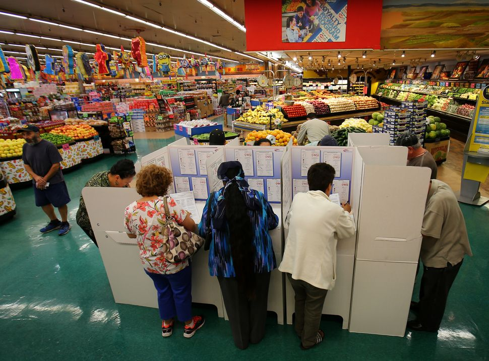 People cast their ballots at a neighborhood grocery store during voting in the 2016 presidential election in National City, C