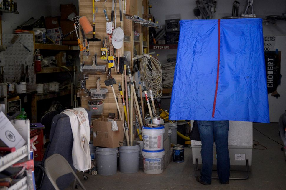 A voter casts his ballot inside the garage of Chobert Decorators during the U.S. presidential election in Philadelphia, Penns