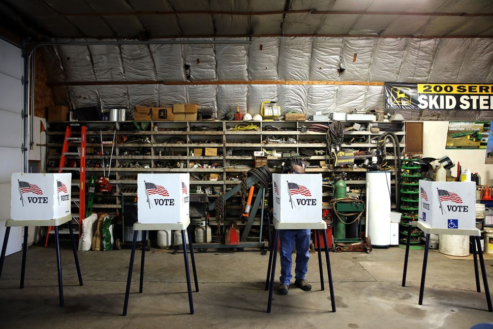 Voters cast their ballots at a polling station set up in a garage during the U.S. presidential election, near Fernald, Iowa,