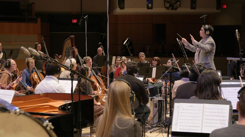 "Darren Fung conducting the orchestra he led for ""The Great Human Odyssey"" score"
