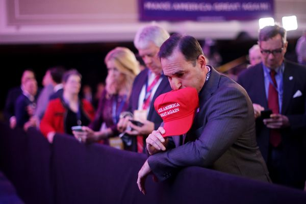 A supporter of Republican presidential nominee Donald Trump watches early results during the election night event at the New