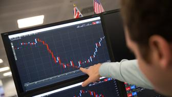 A trader points to a screen showing a dip in market activity that occured on the DAX Futures Index at around 0500 GMT, as he works at ETX Capital in central London on November 9, 2016, following the result of the US presidential election. Global stock markets sank Wednesday after Republican maverick Donald Trump won the US presidency, fanning fears over the world economy, but London attempted a brief rebound in exceptionally volatile trade. / AFP / DANIEL LEAL-OLIVAS        (Photo credit should read DANIEL LEAL-OLIVAS/AFP/Getty Images)
