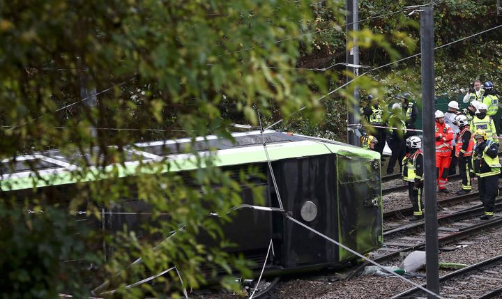 Members of the emergency services work next to a tram after it overturned injuring and trapping some passengers in Croydon, s