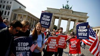 Campaigners pose with 'Stop Trump' signs in front of the Brandenburg Gate to urge Americans living abroad to register and vote in Berlin, Germany, September 23, 2016. REUTERS/Axel Schmidt