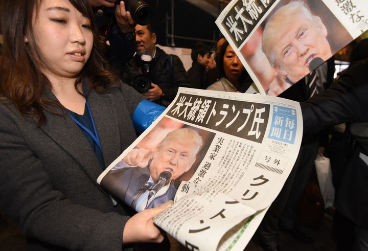 A woman gives out extra editions of a newspaper reporting Trump'svictory. Tokyo, Nov. 9.