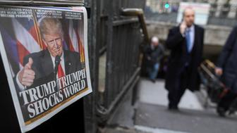A businessman walks past copies of the London Evening Standard newspaper, featuring a picture of U.S. President-elect Donald Trump on its front page, waiting to be picked up in the square mile financial district of the City of London, U.K., on Wednesday, Nov. 9, 2016. Donald Trump was elected the 45th president of the United States in a stunning repudiation of the political establishment that jolted financial markets and likely will reorder the nation's priorities and fundamentally alter America's relationship with the world. Photographer: Chris Ratcliffe/Bloomberg via Getty Images