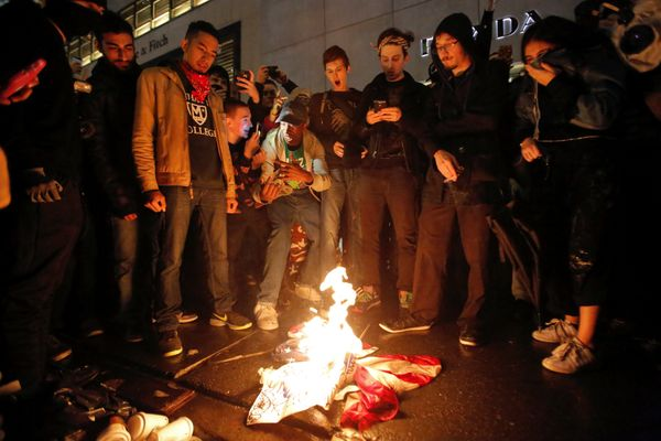 Demonstrators burn the U.S. flag outside Trump Tower during a march against President-elect Donald Trump in Manhattan, New Yo