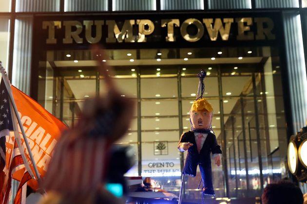 Protesters hoist an effigy of Trump outside Trump