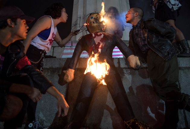 Protesters burn an effigy of Donald Trump in Lee Circle before a march through New