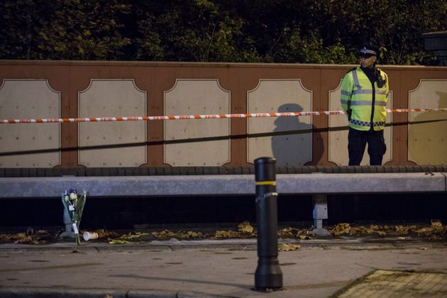 A police officer stands by floral tributes left for the victims of the derailed
