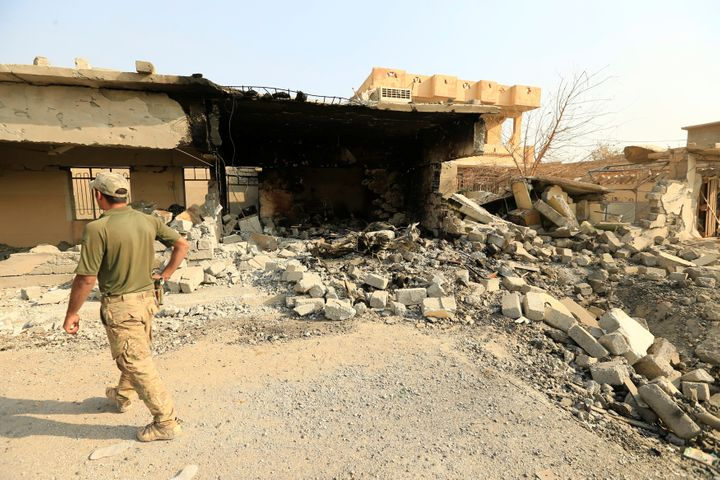 A member of Iraqi security forces walks past a destroyed building by clashes in Hammam al-Ali, south of Mosul, Iraq November