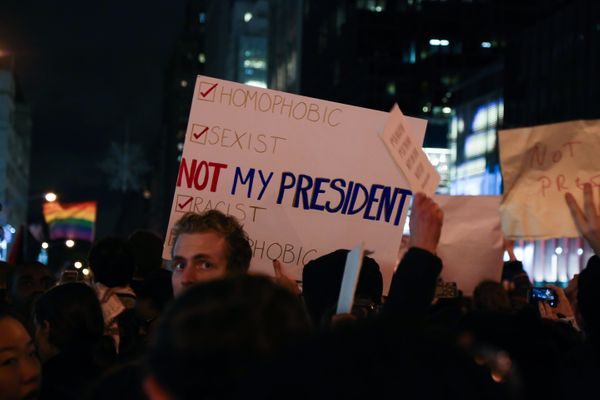 People hold signs during a protest against a Trump presidency in New York City