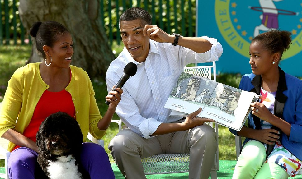 Obama acts out a part of the story while reading from the book <i>Where The Wild Things Are</i>with first lady Michelle