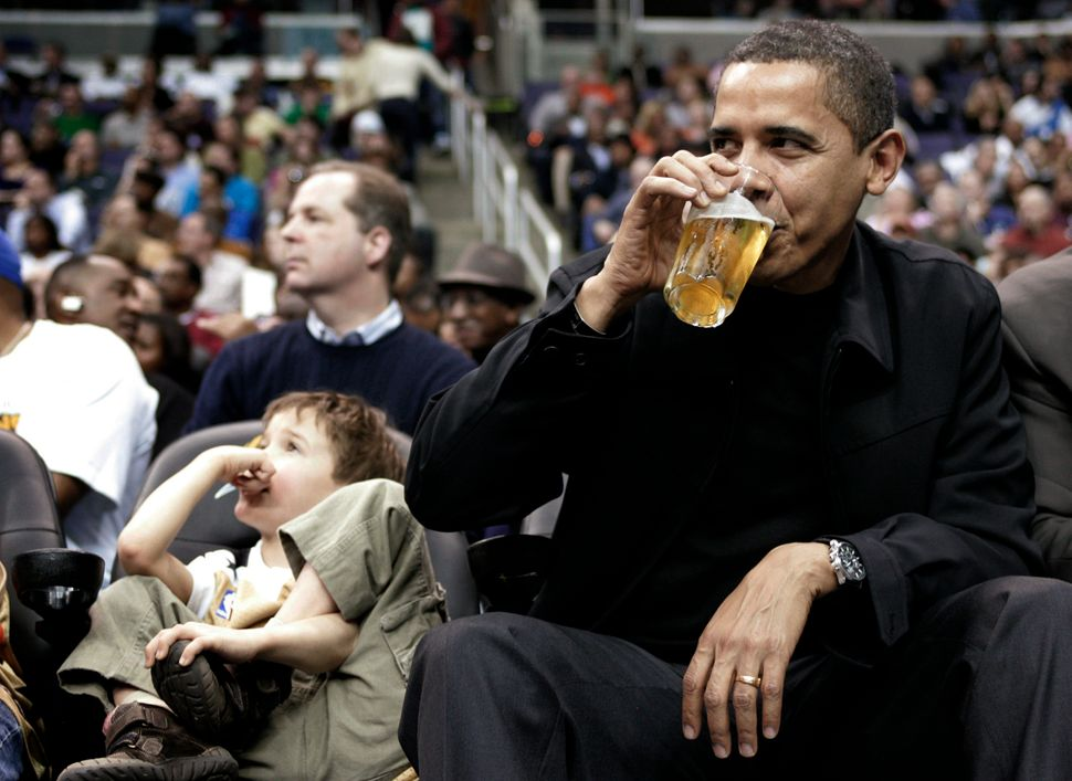 Obama, sitting next to 5-year-old Nick Aiello (L), sips his beverage while attending the Washington Wizards NBA basketball ga