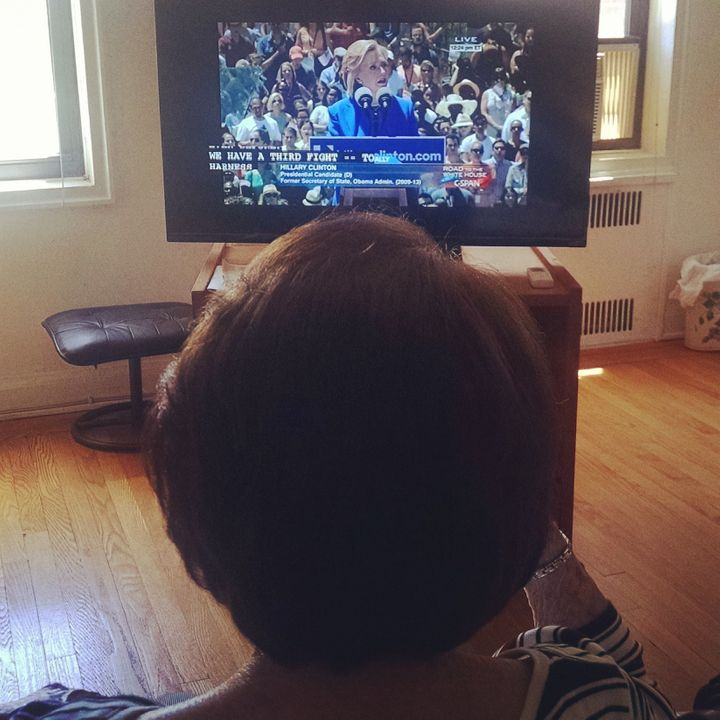 The author's grandmother watches Hillary Clinton's campaign launch, April 2015.