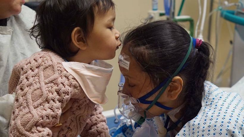 One day after delivering her child, Prasha Tuladhar's lungs failed. Here, Prasha's healthy daughter kisses her forehead.