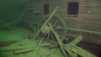 The helm wheel is seen leaning against the wrecks starboard side