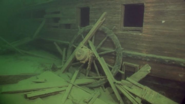 The helm wheel is seen leaning against the wreck's starboard side.