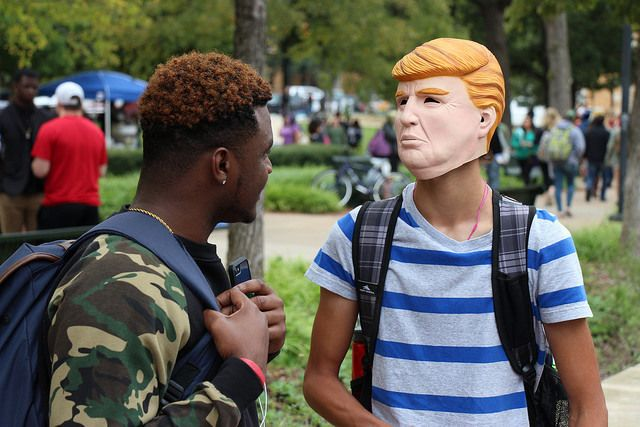 UNT student Aquarius Dickens discussing with another student masked as Donald Trump