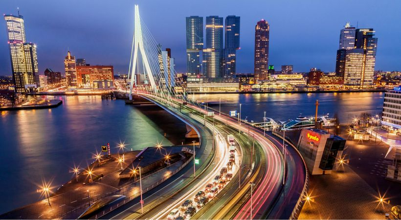<em>Evening view of Rotterdam skyline and waterfront with the suspension cables of the city's emblematic Erasmus Bridge i