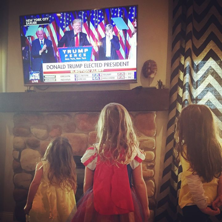 Three of my four daughters standing and staring at the television as Donald Trump is announced President Elect.