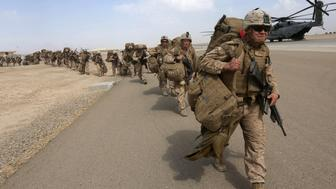U.S. Marines prepare to depart upon the end of operations for Marines and British combat troops in Helmand October 27, 2014. A fleet of planes and helicopters airlifted the last U.S. and British forces from a key base in southern Afghanistan on Monday, a day after the international coalition closed the massive facility and handed it over to the Afghan military. REUTERS/Omar Sobhani (AFGHANISTAN - Tags: MILITARY CONFLICT POLITICS)