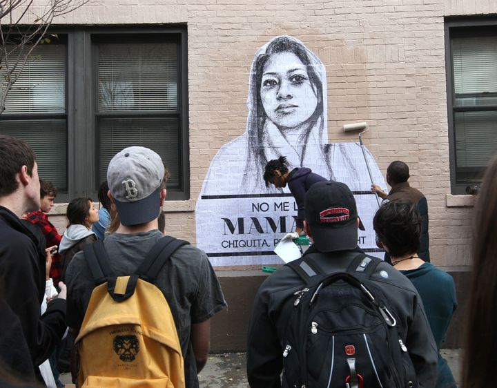 "Artist Tatyana Fazlalizadeh draws a crowd as she installs a wheat-pasting project message, ""Stop Telling Women to Smile,"" on"