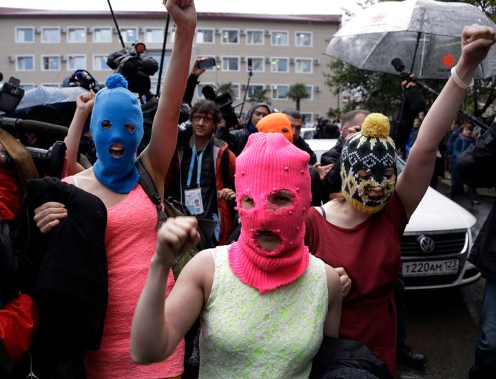 Russian punk group Pussy Riot members wearing pink and blue balaclava make their way through a crowd after they were rel