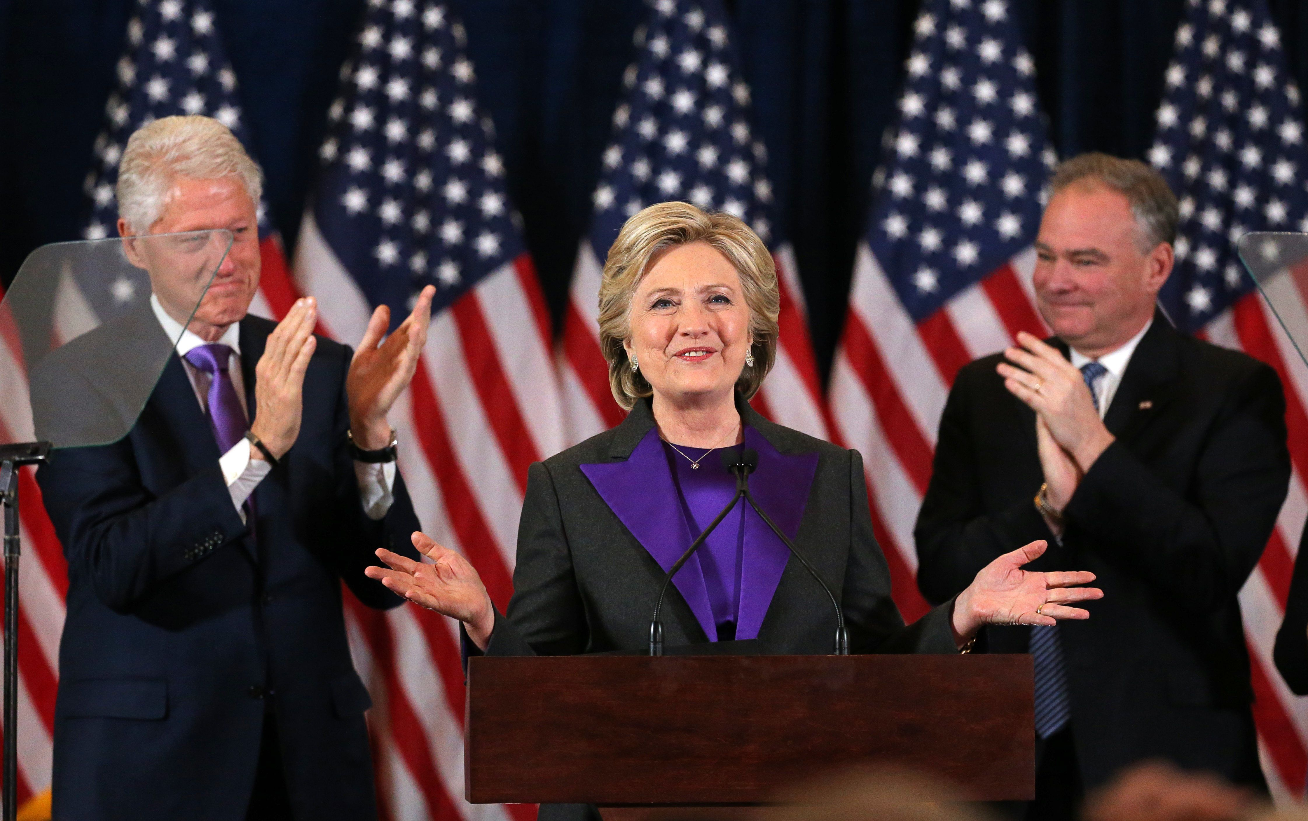 Democratic presidential candidate Hillary Clinton, with her husband, former U.S. President Bill Clinton, (L), and her Vice-President running mate Tim Kaiine (R), applaud at her concession speech to President-elect Donald Trump in New York, U.S., November 9, 2016.        REUTERS/Carlos Barria    TPX IMAGE OF THE DAY