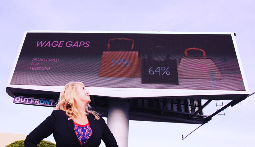 Billboard in Oakland, CA provided by For Freedoms featuring Michele Pred's work. Each purse represents how much women make ac