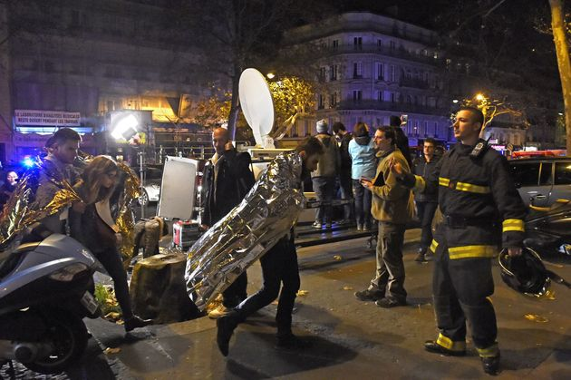People wearing survival blankets walk by a rescuer near the Bataclan concert hall in central Paris, early...