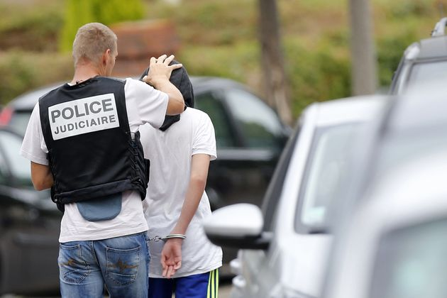 A French policeman arrests a man following a house raidon July 26, 2016 in Saint-Etienne-du-Rouvray,...