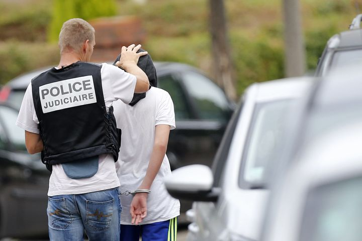 A French policeman arrests a man following a house raidon July 26, 2016 in Saint-Etienne-du-Rouvray, wheretwo men