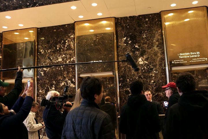Michael Moore speaks to an attendant outside the lobby elevator bank in Trump Tower. He tried to arrange a meeting with the p